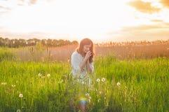 Το κορίτσι έκλεισε τα μάτια της, προσευμένος σε έναν τομέα κατά τη διάρκεια του όμορφου ηλιοβασιλέματος Χέρια που διπλώνονται στη στοκ φωτογραφίες