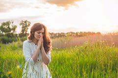 Το κορίτσι έκλεισε τα μάτια της, προσευμένος σε έναν τομέα κατά τη διάρκεια του όμορφου ηλιοβασιλέματος Χέρια που διπλώνονται στη στοκ εικόνα με δικαίωμα ελεύθερης χρήσης