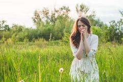 Το κορίτσι έκλεισε τα μάτια της, προσευμένος σε έναν τομέα κατά τη διάρκεια του όμορφου ηλιοβασιλέματος Χέρια που διπλώνονται στη στοκ φωτογραφία με δικαίωμα ελεύθερης χρήσης