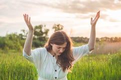 Το κορίτσι έκλεισε τα μάτια της, προσευμένος σε έναν τομέα κατά τη διάρκεια του όμορφου ηλιοβασιλέματος Χέρια που διπλώνονται στη στοκ εικόνα