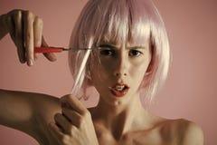 Το κορίτσι έκοψε την τεχνητή τρίχα με το ψαλίδι Στοκ Φωτογραφία