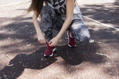 Το κορίτσι δένει τις δαντέλλες Στοκ Εικόνες