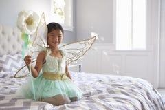 Το κορίτσι έντυσε στη συνεδρίαση κοστουμιών νεράιδων στο κρεβάτι στο σπίτι Στοκ Εικόνες