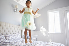 Το κορίτσι έντυσε στο κοστούμι νεράιδων πηδώντας στο κρεβάτι στο σπίτι Στοκ Φωτογραφία