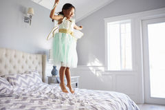 Το κορίτσι έντυσε στο κοστούμι νεράιδων πηδώντας στο κρεβάτι στο σπίτι Στοκ εικόνα με δικαίωμα ελεύθερης χρήσης