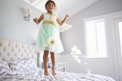 Το κορίτσι έντυσε στο κοστούμι νεράιδων πηδώντας στο κρεβάτι στο σπίτι Στοκ φωτογραφία με δικαίωμα ελεύθερης χρήσης