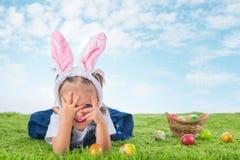 Το κορίτσι έντυσε ως λαγουδάκι Πάσχας στη χλόη με χρωματισμένος Στοκ Φωτογραφία