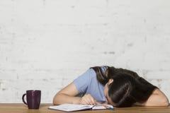 Το κορίτσι έπεσε κοιμισμένο στον πίνακα Δίπλα σε την είναι ένα σημειωματάριο και ένα φλυτζάνι στοκ εικόνες