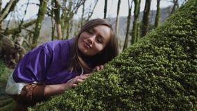 Το κορίτσι έρχεται στο βρύο-καλυμμένο δέντρο και βάζει το κεφάλι της σε το και τις πτώσεις κοιμισμένα απόθεμα βίντεο