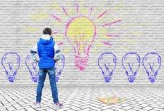 Το κορίτσι έσυρε με τις πολυ χρωματισμένες κιμωλίες σε ένα γκρίζο τούβλο το φωτεινό βολβό ως σύμβολο της δημιουργικής σκέψης Στοκ Εικόνες