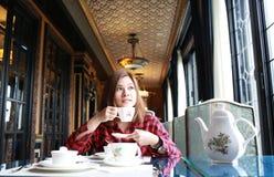 Το κορίτσι έχει έναν χρόνο τσαγιού Στοκ φωτογραφία με δικαίωμα ελεύθερης χρήσης