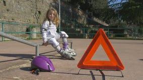 Το κορίτσι έχει το πρόβλημα με το rollerblade στο πάρκο απόθεμα βίντεο