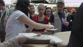 Το κορίτσι δίνει έξω ζωηρόχρωμα doughnuts στους ανθρώπους στο εμπορικό κέντρο δίκαιος Γλυκά φιλμ μικρού μήκους