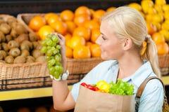Το κορίτσι δίνει την τσάντα εγγράφου με τα φρέσκα λαχανικά επιλέγοντας το σταφύλι Στοκ Φωτογραφία