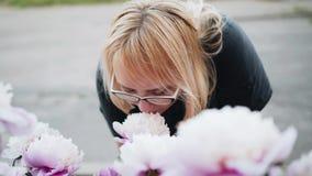 Το κορίτσι αγγίζει ήπια τα λουλούδια στο πάρκο και τα ρουθουνίζει συμπαθητική κινηματογράφηση σε πρώτο πλάνο απόθεμα βίντεο