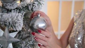 Το κορίτσι αγγίζει το παιχνίδι χριστουγεννιάτικων δέντρων στο χριστουγεννιάτικο δέντρο φιλμ μικρού μήκους