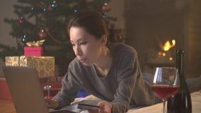 Το κορίτσι αγοράζει το παρόν από την πιστωτική κάρτα on-line κοντά στο χριστουγεννιάτικο δέντρο απόθεμα βίντεο