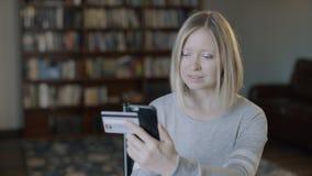 Το κορίτσι αγοράζει on-line να ψωνίσει στο σπίτι με την κάρτα και το τηλέφωνο Τύπος γυναικών χαμόγελου νέος ευτυχής που εισάγει τ απόθεμα βίντεο