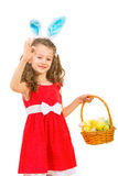 Το κορίτσι λαγουδάκι με το καλάθι Πάσχας παρουσιάζει ο.κ. Στοκ φωτογραφία με δικαίωμα ελεύθερης χρήσης