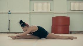Το κορίτσι αθλητικό στηρίζεται, στη γυμναστική, που κάθεται στο σπάγγο και που κάνει την προθέρμανση πρίν εκπαιδεύει φιλμ μικρού μήκους