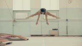 Το κορίτσι αθλητικό χτίζει, στη γυμναστική, εκτελεί ένα ακροβατικό σύνολο απόθεμα βίντεο