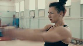 Το κορίτσι αθλητικό χτίζει, στη γυμναστική, κάνοντας την προθέρμανση τ φιλμ μικρού μήκους