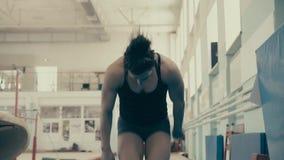 Το κορίτσι αθλητικό χτίζει, στη γυμναστική, που δημιουργείται και κάνει κάνει τούμπα μπροστά απόθεμα βίντεο