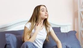 Το κορίτσι αισθάνεται έναν επώδυνο λαιμό Έχει ένα κρύο Ξύπνησε το πρωί και αρρώστησε στοκ φωτογραφία