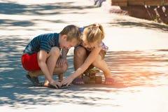 Το κορίτσι αισθάνεται θλιβερό για το αγόρι, ο αδελφός της, ο οποίος τραυματίστηκε οδηγώντας skateboard σε έναν δρόμο στην οδό Στοκ Εικόνες