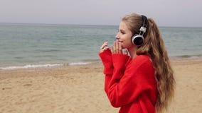 Το κορίτσι ακούει τη μουσική στα μεγάλα ακουστικά στην παραλία θαλασσίως απόθεμα βίντεο