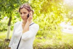 Το κορίτσι ακούει τις λυπημένες ειδήσεις στο τηλέφωνο στο πράσινο θερινό πάρκο Στοκ Φωτογραφίες