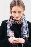 Το κορίτσι δακτυλογραφεί SMS χρησιμοποιώντας το κινητό τηλέφωνο Στοκ Εικόνα