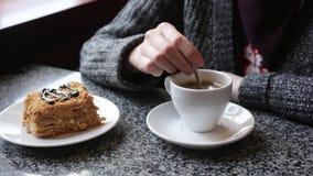 Το κορίτσι ανακατώνει τη ζάχαρη σε ένα άσπρο φλιτζάνι του καφέ Θηλυκά χέρια με ένα φλυτζάνι του americano του espresso απόθεμα βίντεο