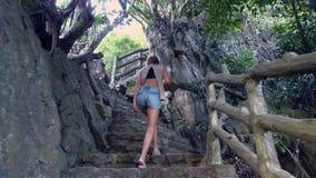 Το κορίτσι αναρριχείται επάνω στα βήματα πετρών με τα κιγκλιδώματα στο παλαιό πάρκο απόθεμα βίντεο