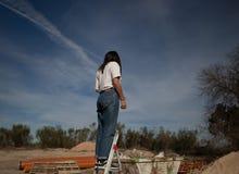 Το κορίτσι αναρριχείται σε μια σκάλα σε ένα βιομηχανικό εξωτερικό στοκ φωτογραφίες με δικαίωμα ελεύθερης χρήσης