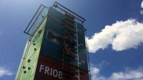 Το κορίτσι αναρριχείται στη σκάλα βημάτων σε έναν υψηλό κάθετο τοίχο απόθεμα βίντεο
