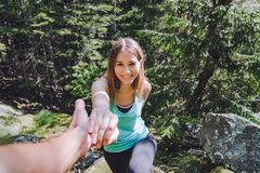 Το κορίτσι αναρριχείται στο βράχο, ο συνεργάτης βγάζει το χέρι για τη βοήθεια στοκ φωτογραφία