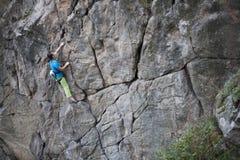 Το κορίτσι αναρριχείται στο βράχο Στοκ Εικόνα