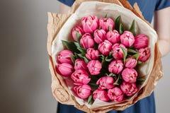Το κορίτσι ανθοκόμων με τα peony λουλούδια ή η ρόδινη νέα γυναίκα τουλιπών ανθίζει την ανθοδέσμη για την ημέρα της μητέρας γενεθλ Στοκ Εικόνες