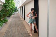 Το κορίτσι ανοίγει την πόρτα στο δωμάτιο ξενοδοχείου Μια νέα γυναίκα θέλει να πάρει στο δωμάτιό σας στοκ φωτογραφίες με δικαίωμα ελεύθερης χρήσης