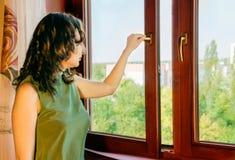 Το κορίτσι ανοίγει το παράθυρο στοκ φωτογραφία με δικαίωμα ελεύθερης χρήσης