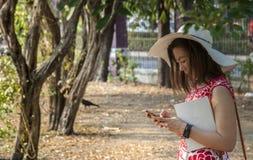 Το κορίτσι ανοίγει το smartphone για να δει το μήνυμα στον κήπο στοκ εικόνα με δικαίωμα ελεύθερης χρήσης