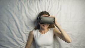Το κορίτσι απολαμβάνει το τιμόνι VR στο κρεβάτι απόθεμα βίντεο