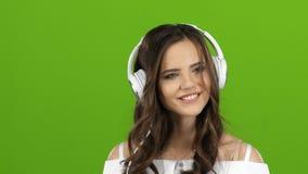 Το κορίτσι απολαμβάνει τη μουσική μέσω των ακουστικών και τραγουδά εμπρός πράσινη οθόνη κλείστε επάνω φιλμ μικρού μήκους