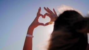 Το κορίτσι από τα χέρια έκανε μια μορφή καρδιών στο ηλιοβασίλεμα, στη θάλασσα, σε ένα πορτοκαλί κλίμα Έννοια: αγάπη που χαλαρώνει απόθεμα βίντεο