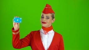 Το κορίτσι αυξάνει μια κάρτα και παρουσιάζει τα σημεία ένα χέρι σε την πράσινη οθόνη απόθεμα βίντεο