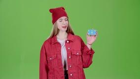 Το κορίτσι αυξάνει μια μπλε κάρτα και παρουσιάζει τους αντίχειρες πράσινη οθόνη κίνηση αργή φιλμ μικρού μήκους