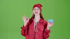 Το κορίτσι αυξάνει μια μπλε κάρτα και παρουσιάζει τους αντίχειρες και παρουσιάζει εντάξει πράσινη οθόνη κίνηση αργή απόθεμα βίντεο