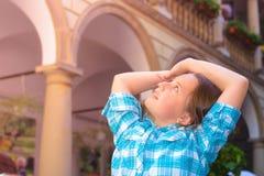 Το κορίτσι αυξάνει τα όπλα της θαυμαστά και εξετάζει πίσω από το κεφάλι το φως του ήλιου Στοκ Φωτογραφία