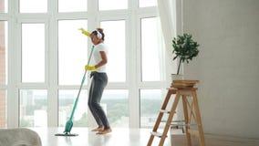 Το κορίτσι αφροαμερικάνων κάνει τα οικιακά συμπαθητικό καθαρό σε επίπεδο, η νέα γυναίκα το πάτωμα και έχει τη διασκέδαση ακούοντα φιλμ μικρού μήκους
